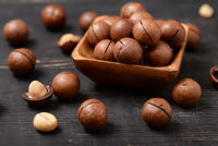 Group of macadamia nuts on  black wooden table