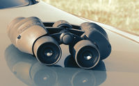 Binoculars lying on the hood of the car.