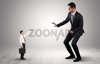 Small businessman pointing to a giant businessman