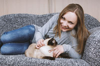 happy young woman relaxing on couch with cat