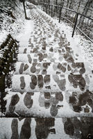 long snow covered stairs in winter with foot steps and tracks