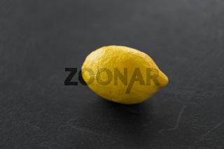 close up of whole lemon on slate table top
