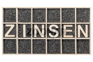 Word ZINSEN in a box on black sand