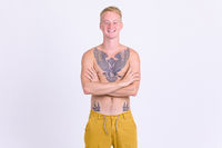 Happy young blonde shirtless man with tattoos crossing arms