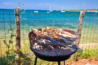 Fish on the grill by the mediterranean beach, idyllic vacation food preparing
