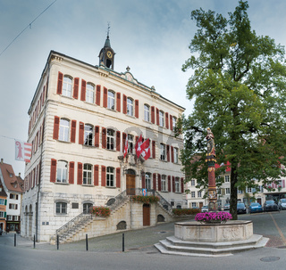 view of the historic 'Fontaine de la Vierge' or Fountain of the holy Virgin and city hall in the Swiss city of Delemont