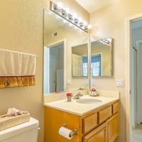 Square frame Vanity area and toilet inside the bathroom of a home with brown floor