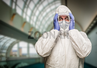 Man Holding Head With Hands Wearing HAZMAT Protective Clothing Inside Building