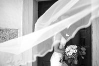 The kiss. Bride and groom kisses tenderly in the shadow of a flying veil. Artistic black and white wedding photo.