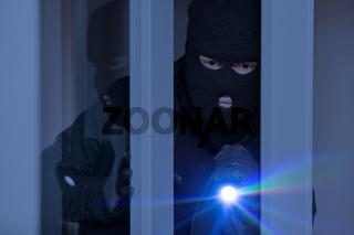 Einbrecher nachts an Fenster vom Haus