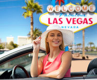 happy young woman in convertible car at las vegas