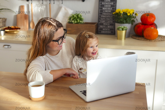 Beautiful mom working at home on a laptop computer while taking care of her baby girl