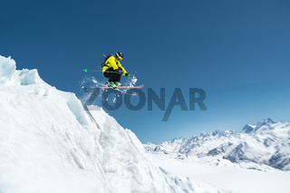 A skier in full sports equipment jumps into the precipice from the top of the glacier against the background of the blue sky and the Caucasian snow-capped mountains. Elbrus region. Russia