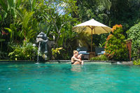 Happy couple kissing while relaxing in outdoor spa infinity swimming pool surrounded with lush tropical greenery of Ubud, Bali. Luxury spa and wellness vacation retreat concept