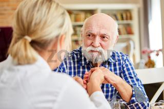 Pflegedienst Frau tröstet dementen Senior