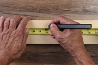 High angle closeup of a carpenters hands using a tape measure to mark a cut line on a board.