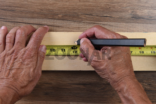 High angle closeup of a carpenters hands using a tape measure to mark a cut line on a board