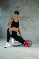 Happy healthy smiling woman working out with fitness roller at the gym