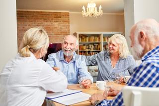 Senioren und Ärztin in einer Gruppentherapie