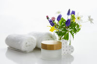 Towels with heart next to a cream box in front of white background and flowers in a vase.
