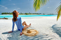 Woman sitting on beach under palm tree