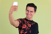 Portrait of young handsome man taking selfie