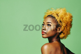 Beautiful young girl with bleached curly hair and bare shoulder looking up, in front of a green background
