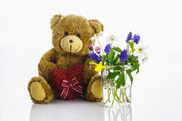 A teddy bear with a heart next to a vase with little flowers. Spring is here.