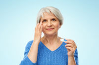 senior woman applying contact lenses over blue