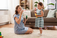 pregnant mother and daughter blowing soap bubbles