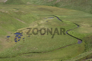 Panorama from the top of the river floodplain with tundra lakes between two hills on a summer day
