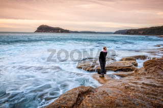 Female standing on rocks letting coastal waves wash up to her feet
