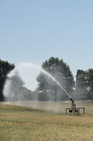 Portable sprinkler irrigation machine spraying water over farmland