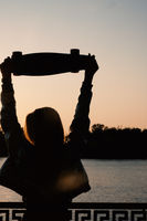 Woman posing with her hands holding skateboard raised up in the sunset sky