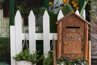 Wooden letter box with plants and white fence