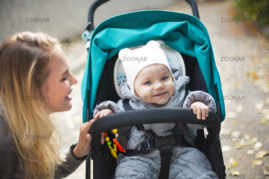 Young blond  woman with stroller going for a walk in a park