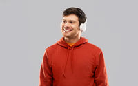 happy young man in headphones and red hoodie