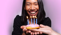 Pretty happy Asian girl blowing candle on birthday cake isolated over gray wall