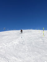 Skier downhill on snowy ski slope in sunny winter day