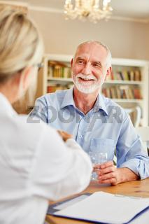 Senior freut sich über den Hausbesuch der Ärztin