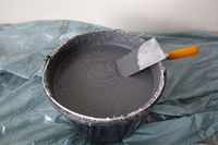 Decorative Plaster and a Trowel in a Bucket