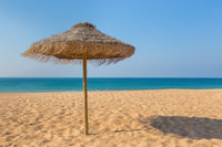 One wicker beach parasol at blue sea
