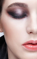 Closeup macro portrait of female face.  Girl with perfect skin and violet - black smoky eyes make-up.