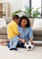 mother and baby playing with soccer ball at home