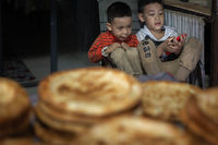 Two boys sitting in a street bakery