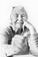Happy 96 years old elderly woman giving a thumb up and looking at camera.