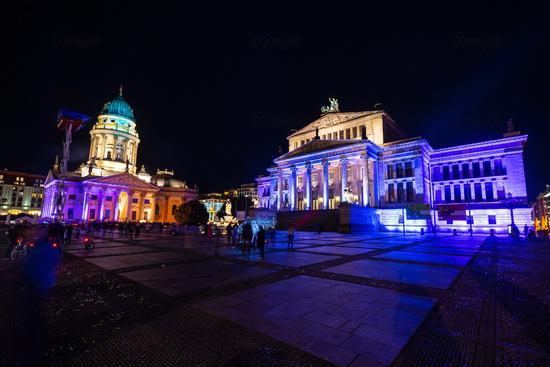 Square Gendarmenmarkt, Konzerthaus and German Church in brightly colored illuminations