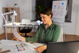 woman working on user interface at night office