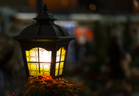 Light lantern street in the dark. Lamp with stained glass windows close-up on a blurred city background