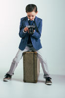 Young boy in suit with camera sitting on suitcase